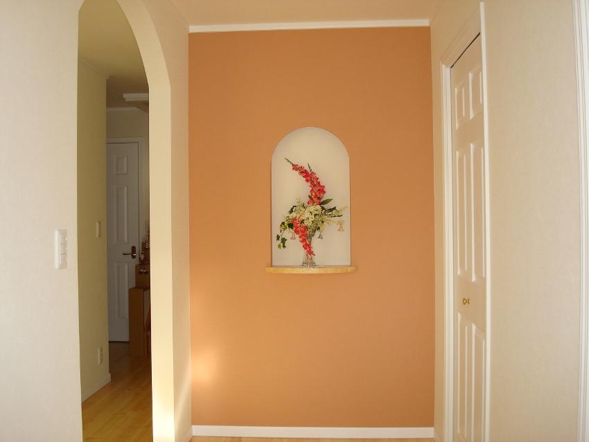 玄関ホール。サーモンピンクのアクセントクロスとニッチがお客様をお出迎え